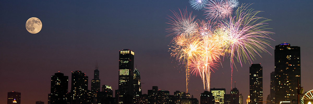 glam shot of fireworks & a full moon over Chicago at night