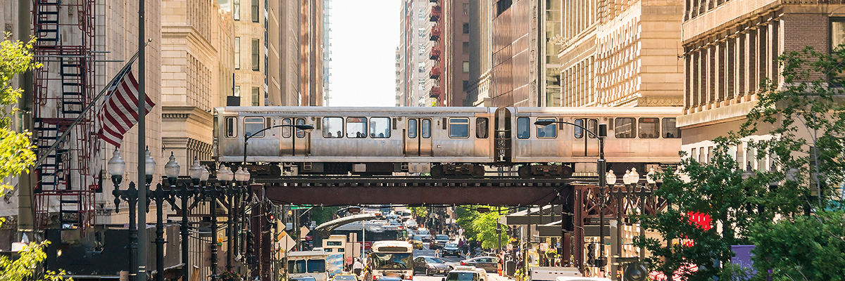 Photo of downtown Chicago showing an EL train over a city street.